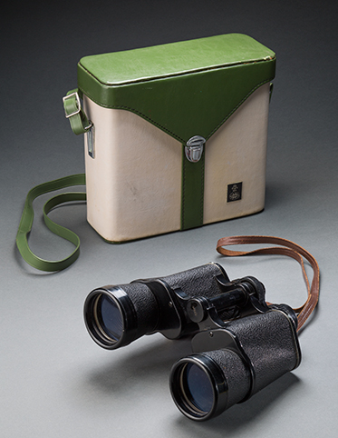 A set of 'YASHICA' brand binoculars, with a black plastic body, and an attached brown leather strap. A 'tasco' brand green and white binoculars case with silver clasp and an attached green shoulder strap.