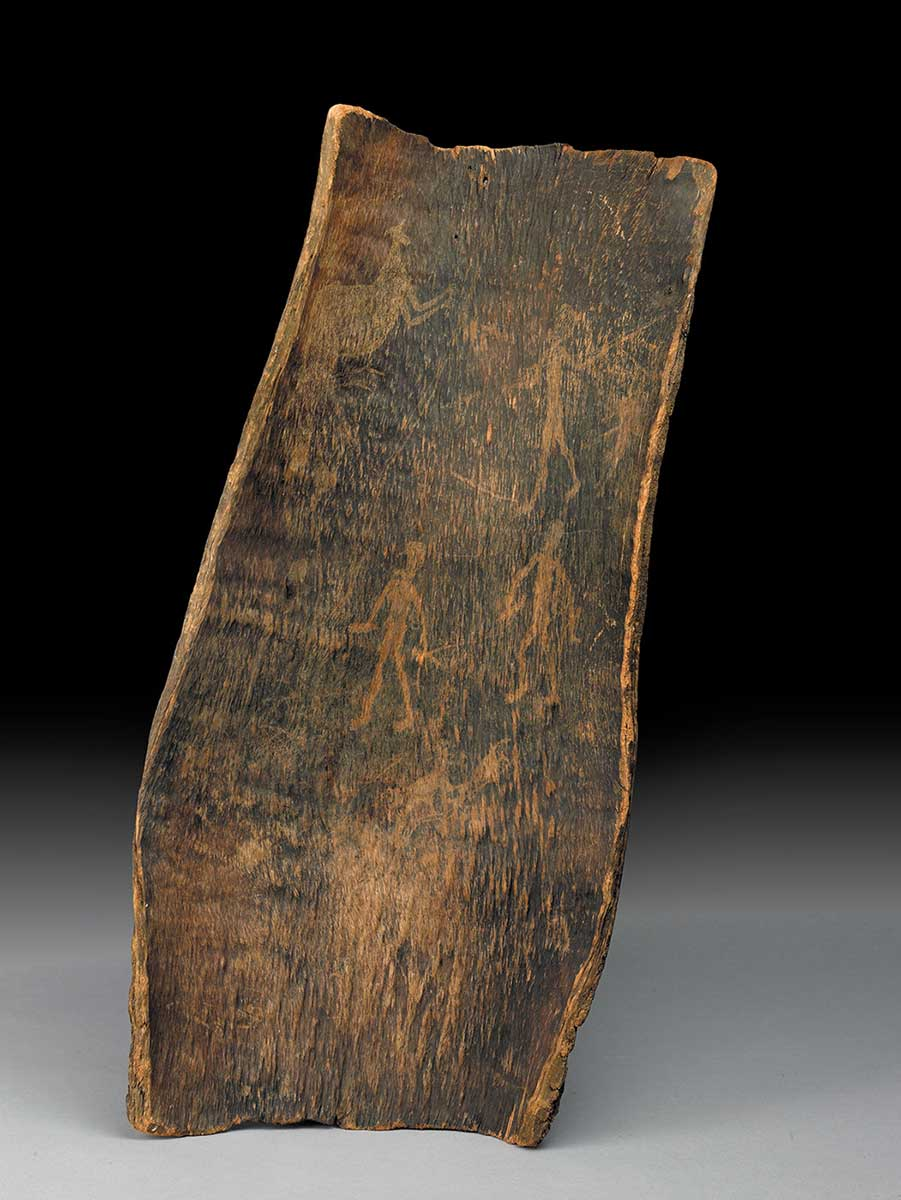 A piece of bark, blackened by fire, on which various figures have been etched, including a human figure pointing a spear at a kangaroo. - click to view larger image