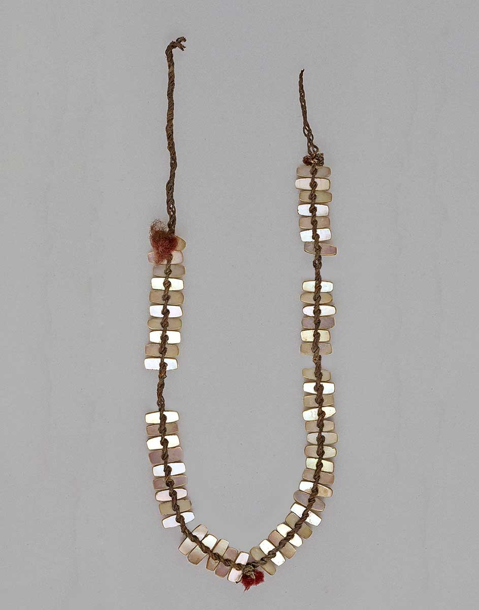 Necklace consisting of a fibre cord adorned with pearl shell. - click to view larger image
