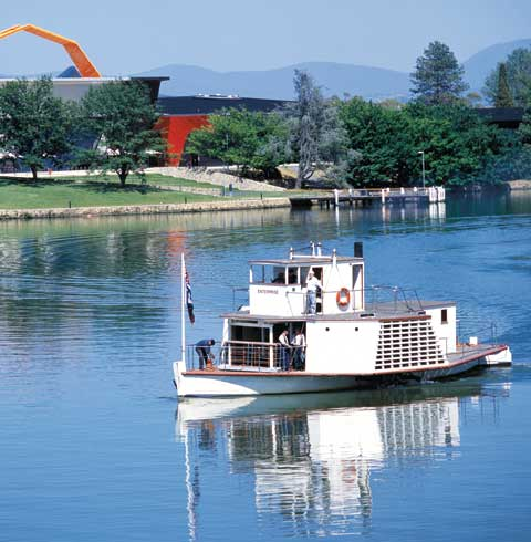 The wooden paddle steamer 'Enterprise' on Lake Burley Griffin, with the National Museum in the background. Four crew members stand on the steamer's deck.