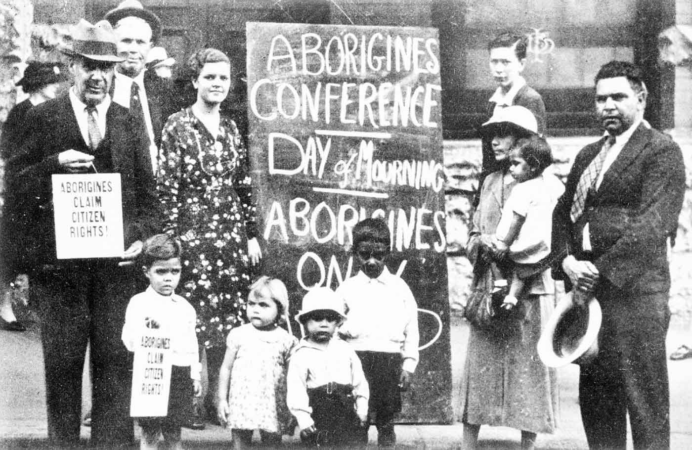 Black and white photo of a group of men, women and children holding protest placards and standing in front of a large banner that includes the text: 'ABORIGINES CONFERENCE'.