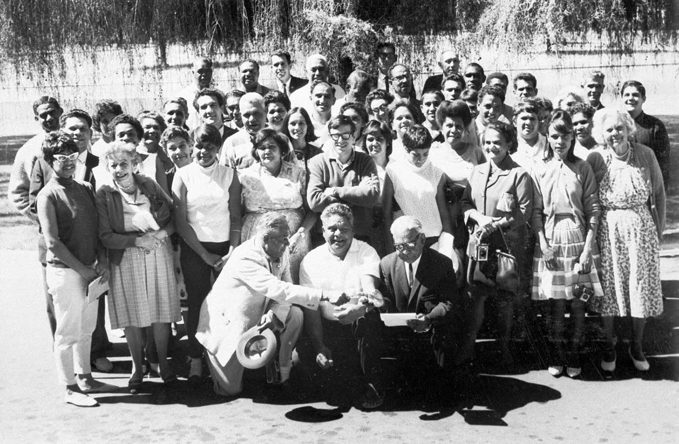 Black and white portrait photo of a large group of men and women.