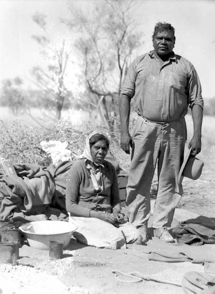 Black and white photo of a man and woman amongst a basin and other domestic objects in bush land. - click to view larger image