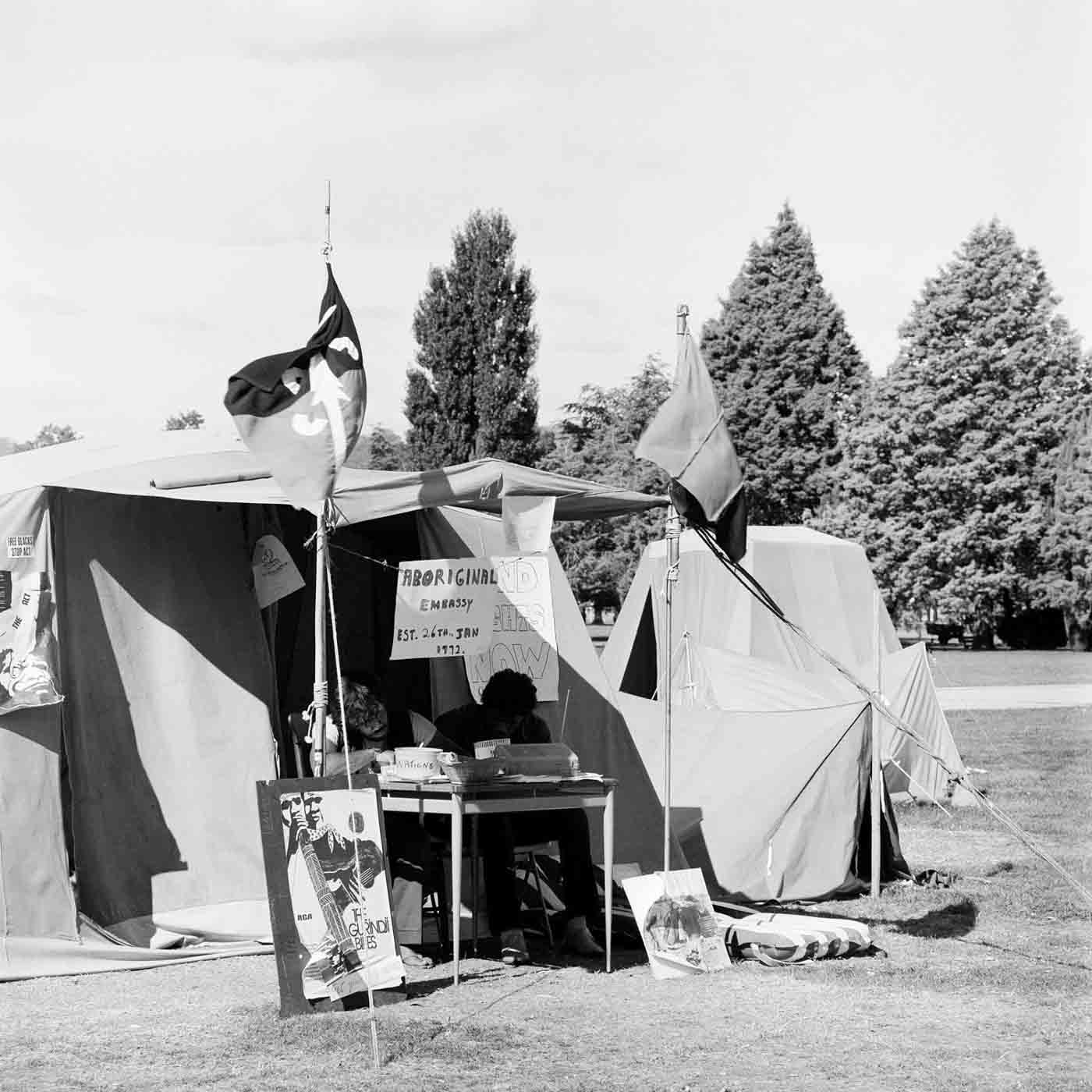 Black and white photo of a two men sitting at a table in front of a tent. There are flags out the front and various protest signs fixed to the tent.