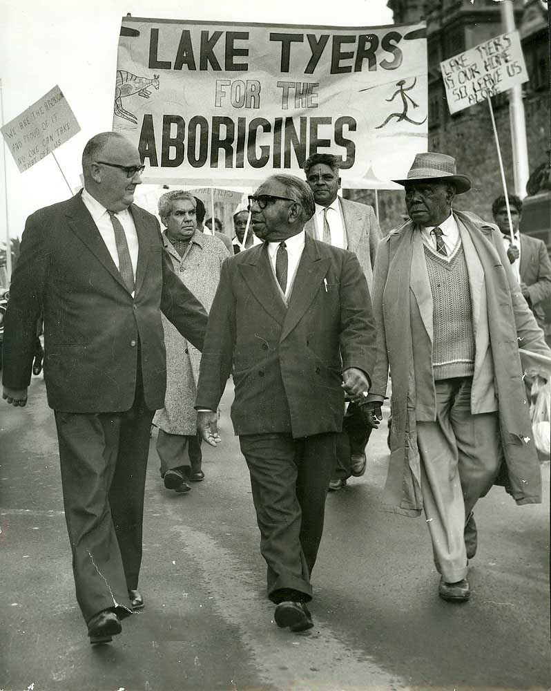 Black and white photo of a protest march with men in business suits. Behind is a banner with the text: LAKE TYERS FOR THE ABORIGINES.