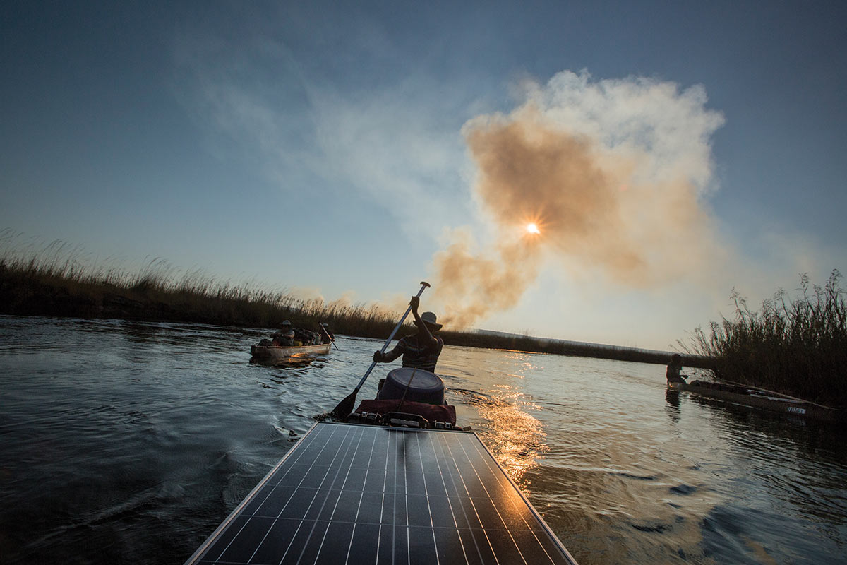 A person at the helm of a raft paddles away from smoke rising behind them in the distance. A large solar panel is on the front of the raft. Two other small watercraft are visible either side of the raft.  - click to view larger image