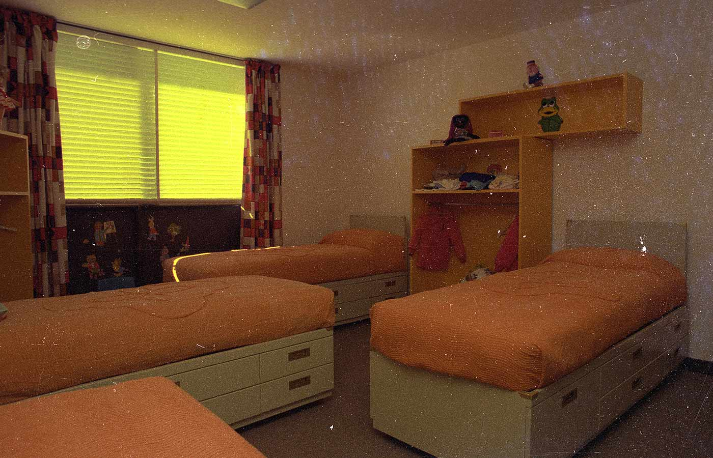 Colour image showing four beds in a room, with orange bedspreads, and drawers under each. Bright yellow shelves on the far wall contain clothes and a toy frog and doll. - click to view larger image
