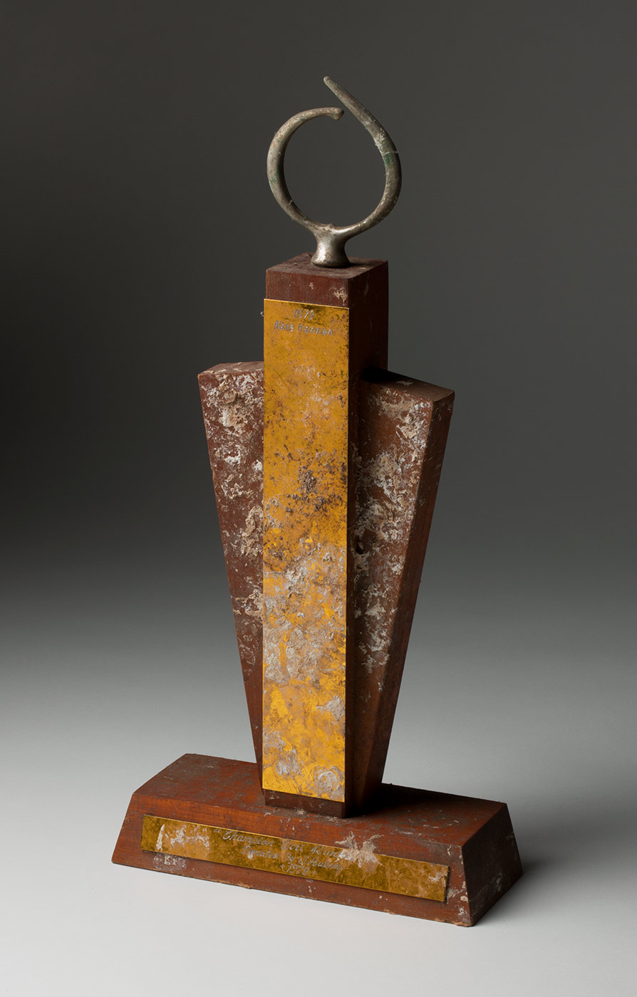 A wooden and metal trophy with two half circles on top. The surface is streaked with bird droppings. - click to view larger image