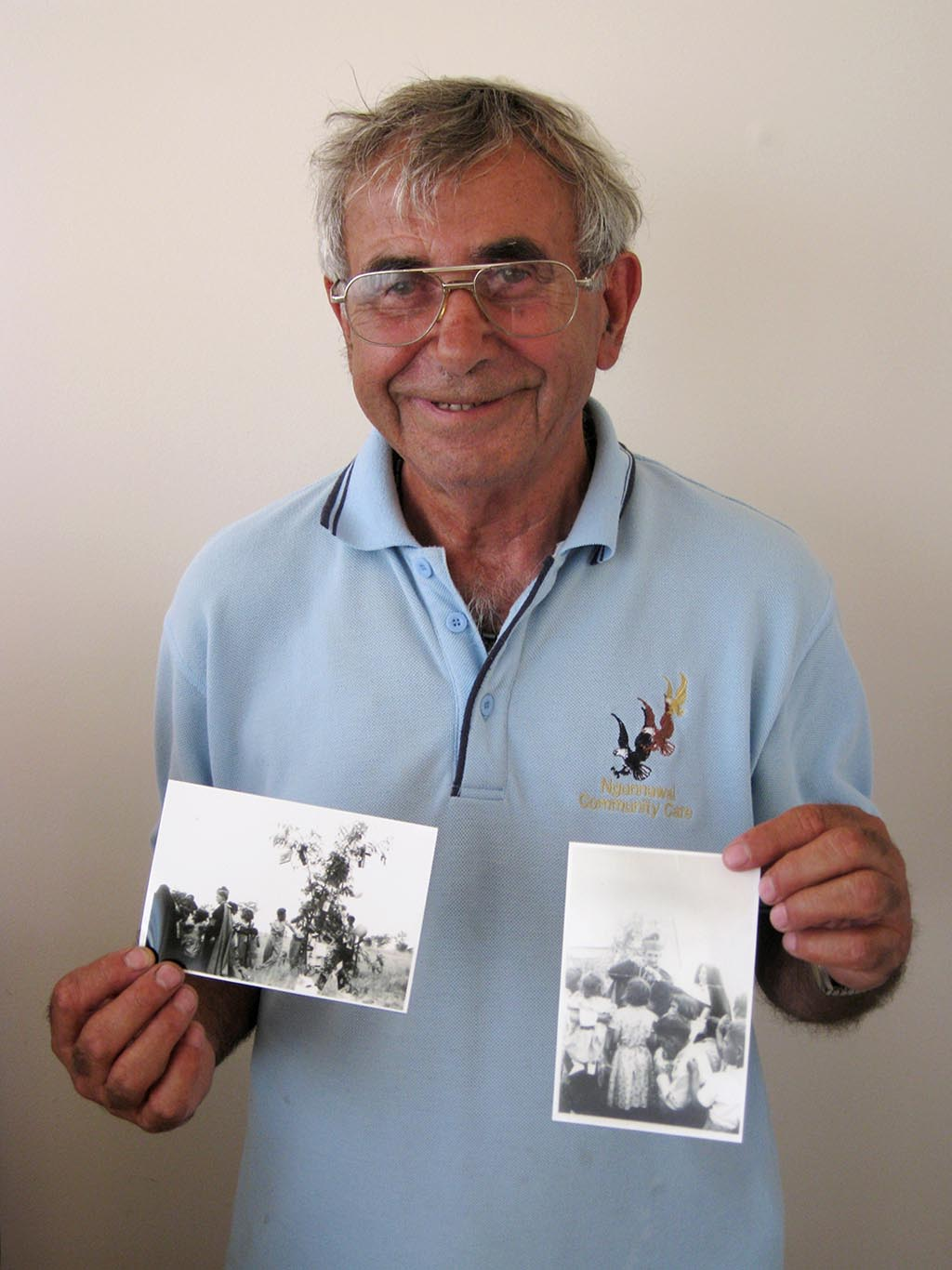 Eric Bell holding two black and white photographs. - click to view larger image