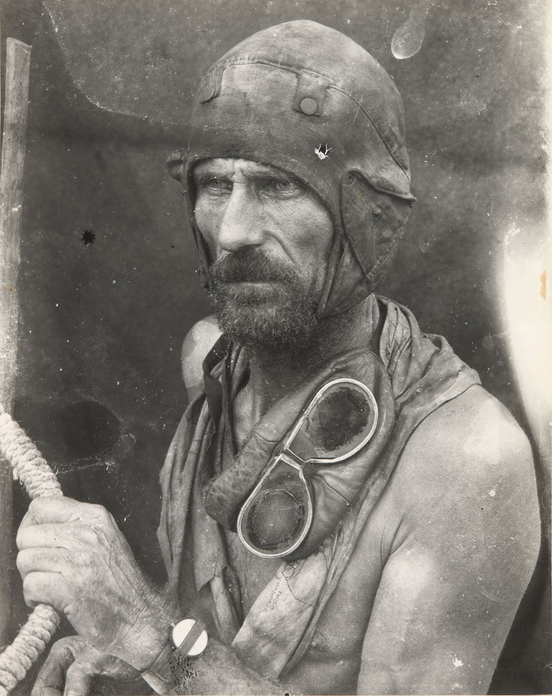 Black and white image showing a bearded and bare-chested man gazing to the left of frame. He wears a leather flying-style cap and has goggles draped around his neck. His right arm clutches a rope. - click to view larger image