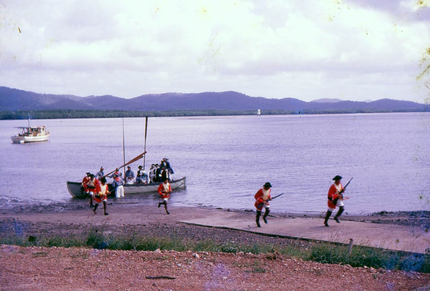 Colour photo of men in costume disembarking a rowboat on a large river and running up a boat ramp. - click to view larger image