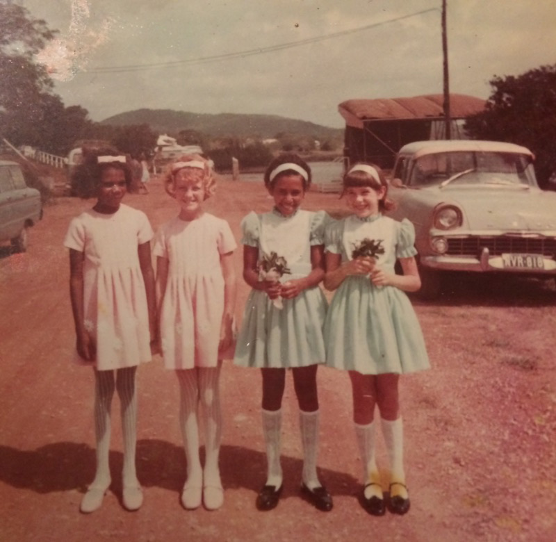 Colour photo of four young girls in handmade dresses and standing on a dirt road in a town. Two are holding flower bouquets. - click to view larger image
