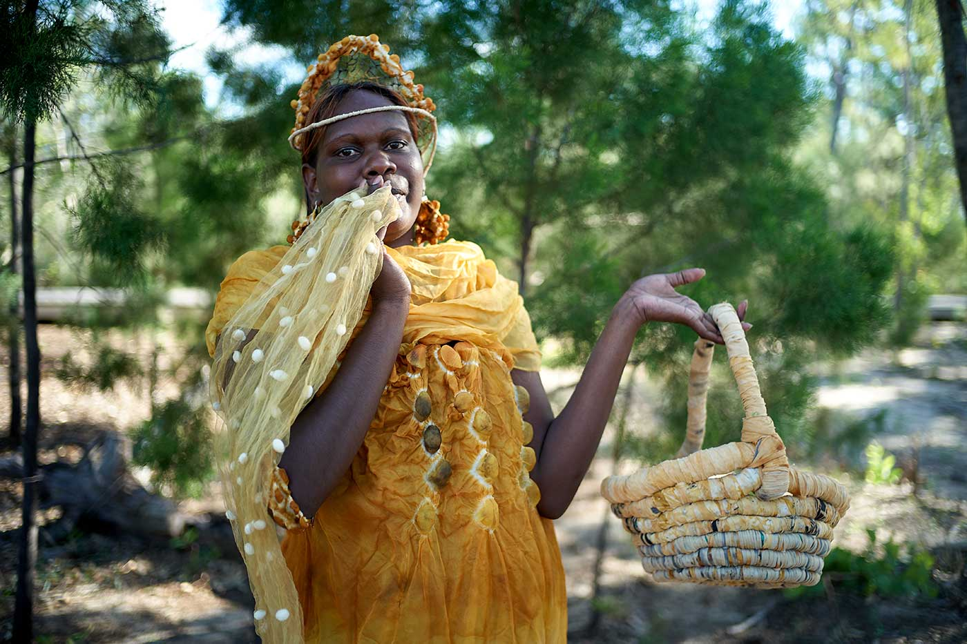 Woman wearing a yellow dress, shawl and hat, and holding a basket - click to view larger image