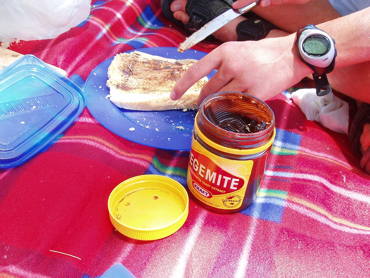 Vegemite being spread onto white bread on a picnic blanket. - click to view larger image