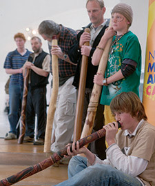Visitors at the Museum learning to play the didgeridu.