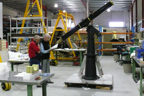 Two men inspect a large telescope