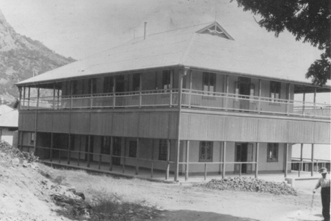 Black and white image of a two-storey building with verandahs.
