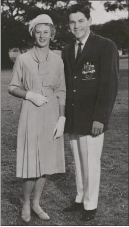 Black and white portrait showing a woman dressed in a knee-length dress and wearing a soft hat, gloves and shoes. A man stands to her right. He wears a dark blazer with an Australian coat of arms on the right breast pocket. He is also wearing a dark necktie, light-coloured trousers and dark shoes.