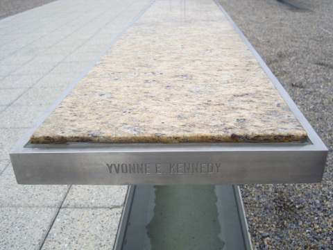 Far end of a silver rectangular metallic bench with a light marble top. 'YVONNE E. KENNEDY' is engraved in the side of the bench, which sits abover a pool of water