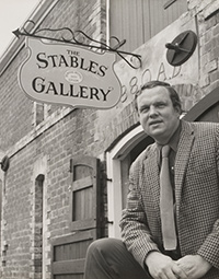 Photograph of Bill Derham in front of the Stables Gallery.