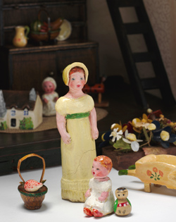 Miniature figures of a young woman and a baby, a basket and flower cart.
