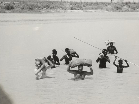 Charles P Mountford, Bill Harney and five Aboriginal men (unidentified) crossing the East Alligator River, 1948.