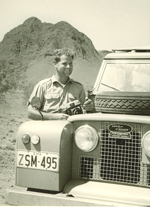 Black and white image showing Bob Edwards standing beside a Landrover, with a rocky formation in the background.
