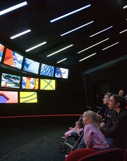 Colour photograph showing five people sitting at the right of a darkened room, looking at three rows of screens on the left. The nine screens show images of various colourful architectural details. Narrow slits of light are visible on the roof of the theatre.