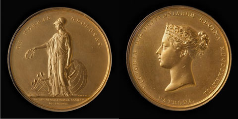Image showing two sides of a gold medal on a black backdrop. The face on the left shows a figure of a woman with a laurel wreath in her right arm and a map in her left, with a sextant and globe behind her. The face on the right shows the profile of a woman wearing a crown.