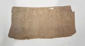 This piece of barkcloth, reddish-beige colour and full of holes around the edges.