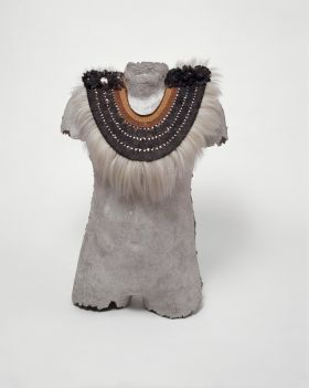 Breastplate of semicircular shape made of cane, plaited coconut fibres and other plant material, Dog hair, shark teeth, feathers and mother-of-pearl are also used.