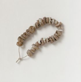 Jewellery & Adornment consisting of thirty-one white and beige-coloured shell discs arranged on a string.