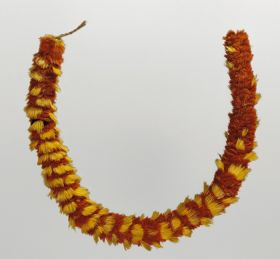Feathered necklace that consists of yellow and red feathers, tightly arranged in circles.