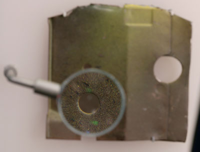 Piece of khaki metal dashboard, with one section magnified for display.
