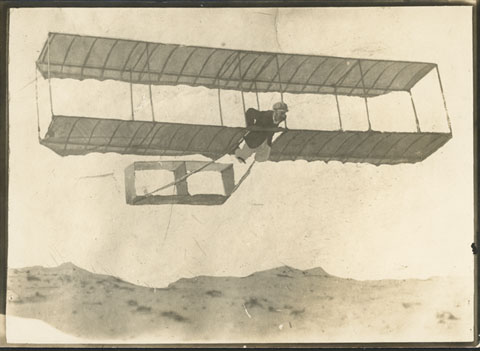 A biplane glider being flown above a sand dune.