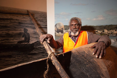 Colour photograph of a man standing behind a partially visible dugout canoe. Images of a canoe and a landscape are partially visible in the background.