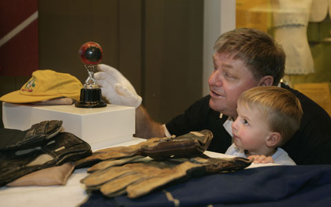 Swan Richards shows a young Museum visitor Wally Grout's record-breaking ball and other cricket gear including a cap and gloves.