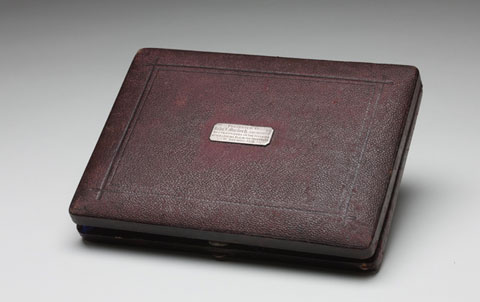 A brown, leather covered case for drawing instruments.