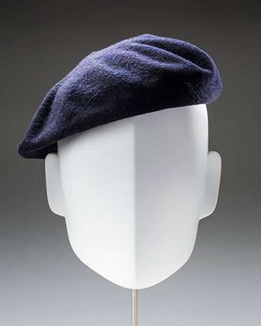 A blue grey beret on a white mannequin