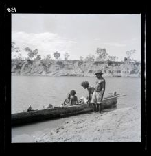 A black and white photographic negative that depicts an Aboriginal man and woman standing on a riverbank next to a canoe with a child and adult sitting in the canoe.