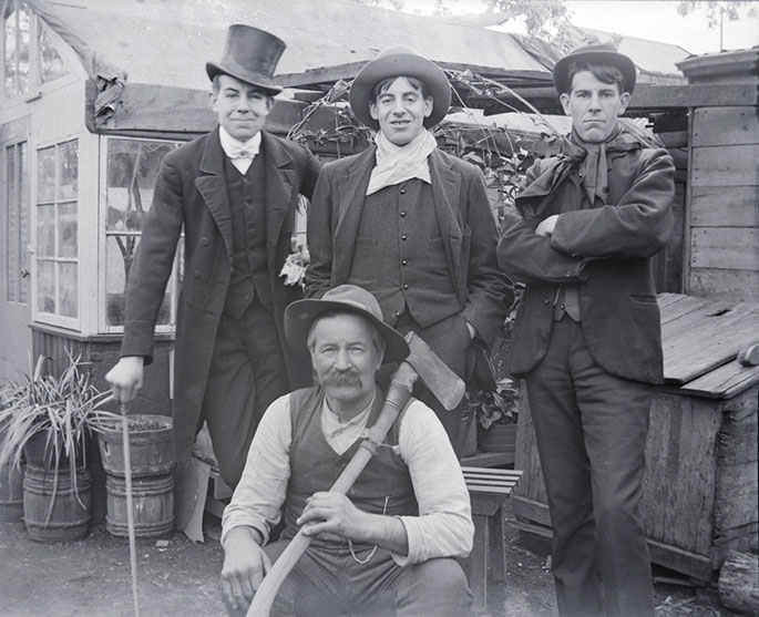 Group portrait of four men posing in front of a dwelling. Three young men stand at rear, wearing dark suits and hats. The man far left leans on a cane. The other two wear scarves. The fourth man, who is older, squats at the front, wearing a vest without a jacket and holding an axe, which rests on his shoulder.