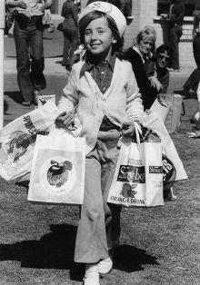 Black and white photo of a child wearing a sailor's hat and pants and carrying mulitple show bags on both arms.