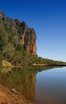 Colour photograph showing the steep walls of a gorge rising above calm water. A crocodile lies in shallow water in the foreground.