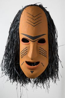 Cultural mask with yellow ochre face, black markings and black hair