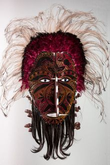 Cultural mask with black face; red, yellow and orange markings; feathers and other materials.