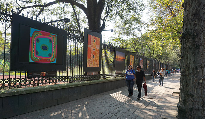 Large graphic panels installed on perimeter fence with pedestrians walking by