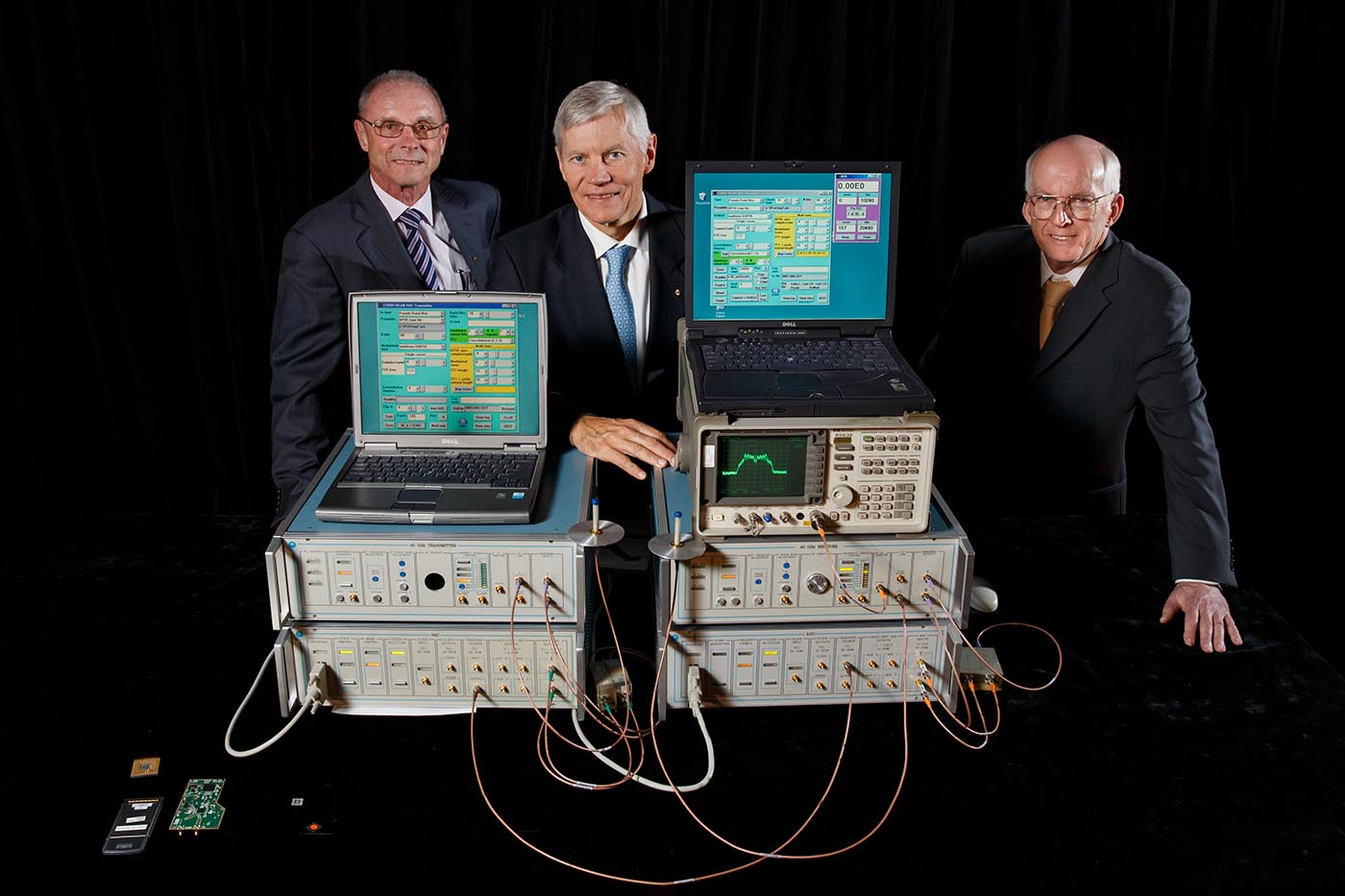 three men in suits standing beside a table on which sit a collection of cumbersome electronic equipment.