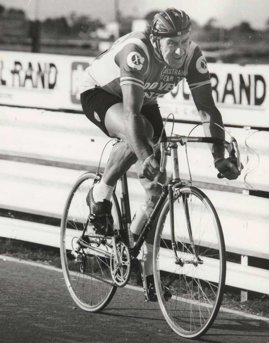 A black and white photo of Jim Coyle on his bicycle. - click to view larger image