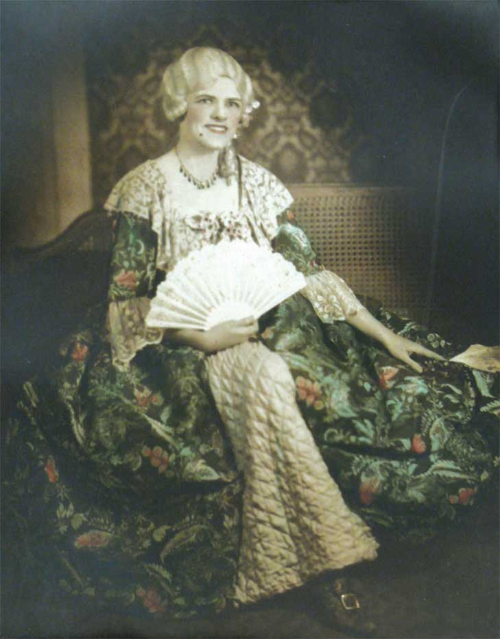An old portrait photo of a woman seated in an elaborate green floral dress. Her hair is white and she is holding a white opened fan with her right hand.  - click to view larger image