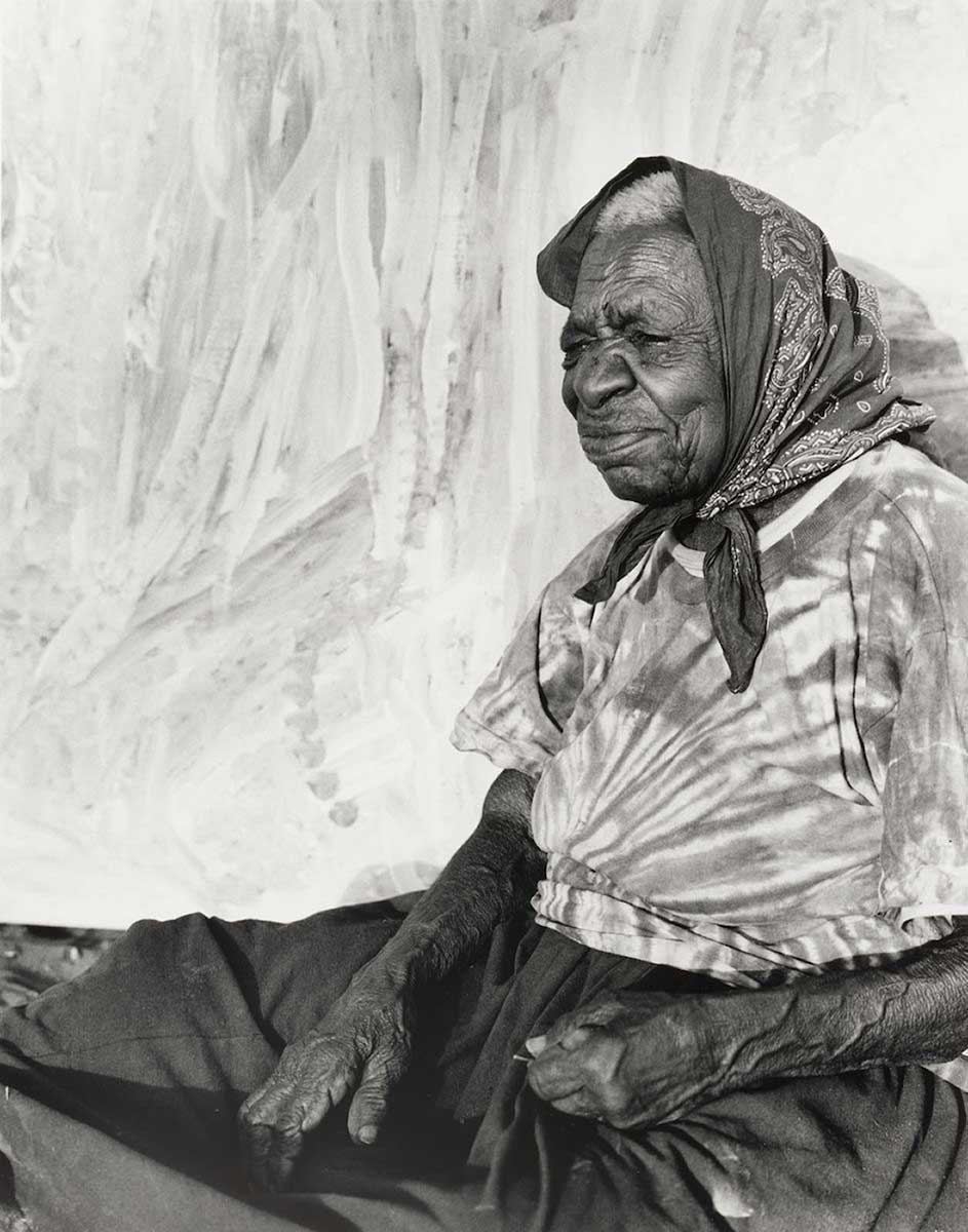 Portrait of an Aboriginal Australian woman sitting in front of a painting. - click to view larger image